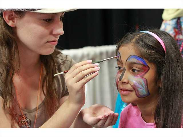 Tanya Mannion of the Canyon Theatre Guild paints the face of Riya Mistry of Chatsworth during Child & Family Center's 10th annual Kid Expo held at Golden Valley High School in Canyon Country on Sunday. Last year's event drew an estimated 7,000 people. Photo by John Lazar.