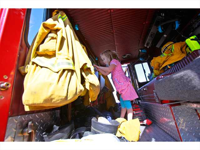 Colleen Westcott, 4, of Santa Clarita looks through Fire Truck 150's cabin while it was parked for kids to look at during the Child & Family Center's 10th annual Kid Expo. Photo by John Lazar.