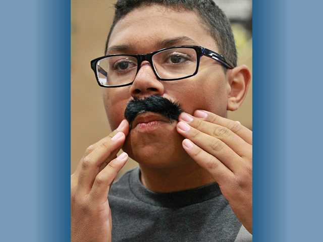 Jordan Lopez, 14, of Valencia applies a fake mustache over his lip during the Sunday expo in Canyon Country. Photo by John Lazar.
