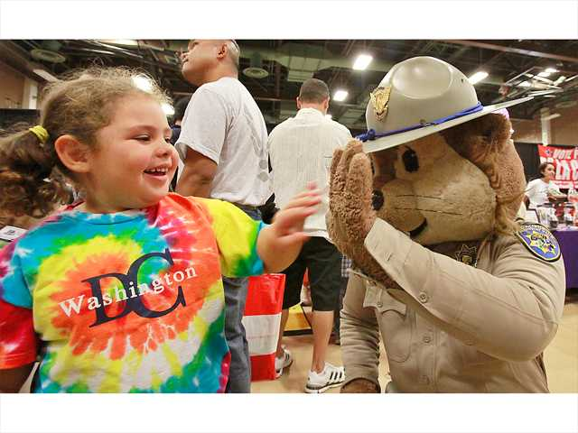 Makayla Sutton, 4, of Saugus, gives Chipper a high-five as he walks around the Child & Family Center's 10th annual Kid Expo held at Golden Valley High School. Photo by John Lazar.
