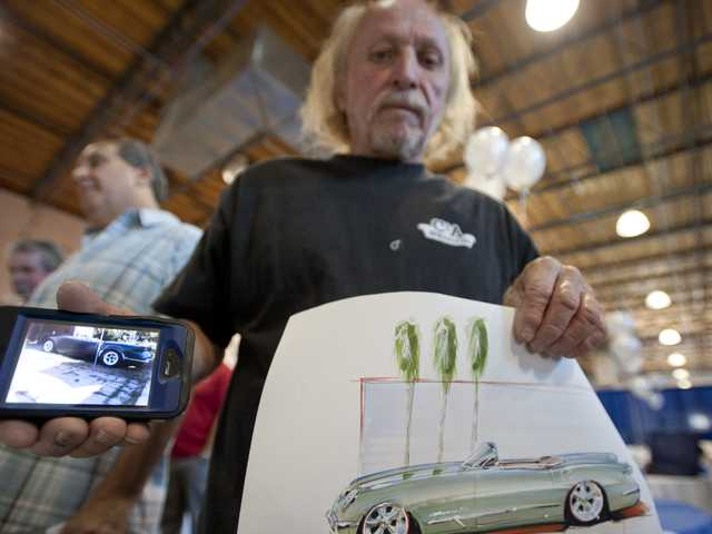 Phil Doleman uses his cellphone to display a photo of the 1954 Corvette he is restoring while also showing a sketch of the car drawn for him by Chip Foose during a fundraiser for fallen law-enforcement officers at the Centre Pointe Collision Center on Wednesday. Signal photo by Charlie Kaijo