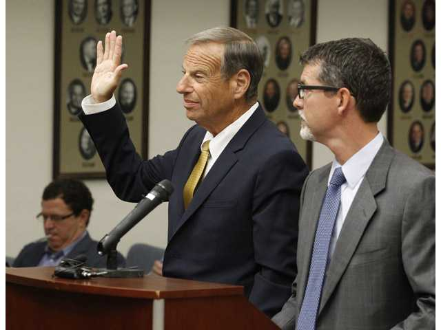Former San Diego Mayor Bob Filner, left, stands with counsel in court and takes an oath before he pleads guilty on state charges of felony false imprisonment Tuesday.