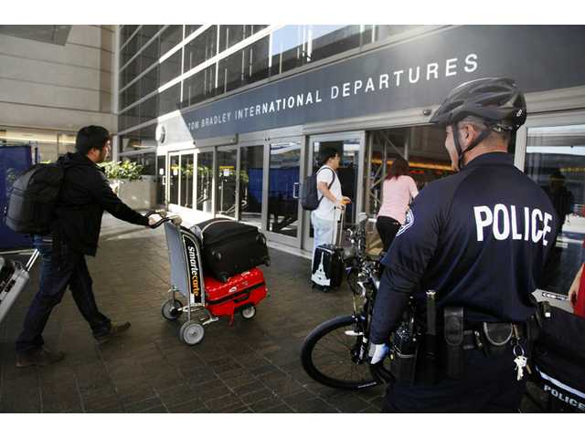 A Los Angeles Police officer patrols outside the departure area at Los Angeles International Airport on Wednesday.