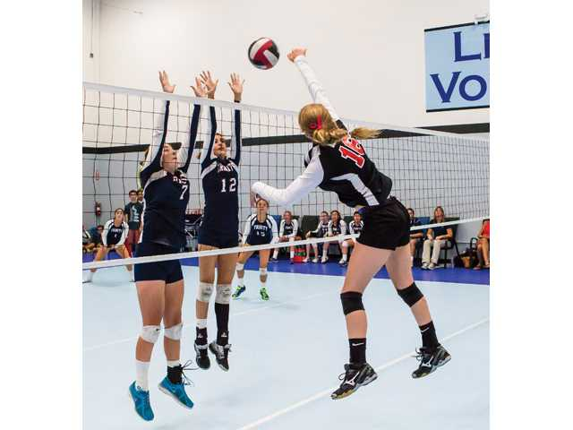 Santa Clarita Christian's Kylie Brown (16) hits the ball over Trinity's Lizzie MacAdam (7) and Sarah Howell (12) on Wednesday at Legacy Volleyball Club. Photo by Wally Caddow/Courtesy photo