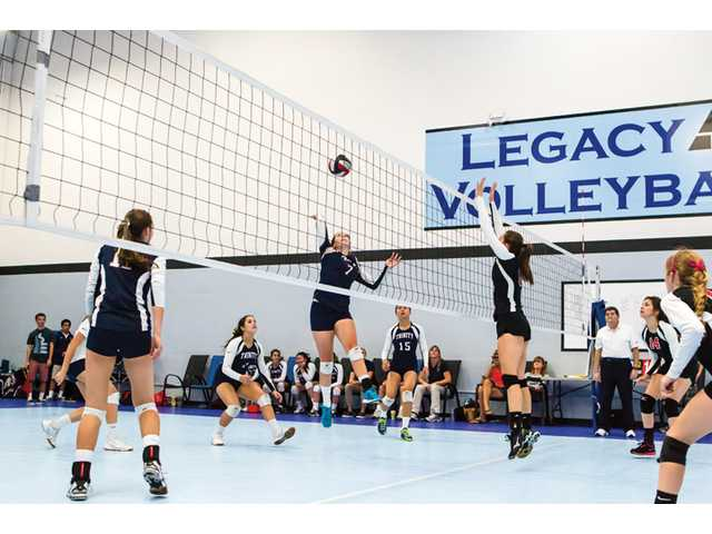 Trinity's Lizzie MacAdam (7) hits the ball as Santa Clarita Christian's Allie Acosta (6) blocks on Wednesday at Legacy Volleyball Club. Photo by Wally Caddow/Courtesy photo