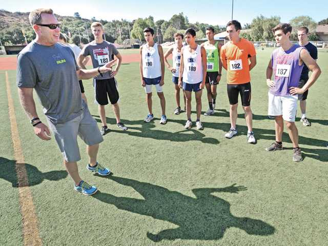 "Sports coordinator Mark Ellis, left, describes how filiming will take place for runners if they are picked to appear in the Disney film ""McFarland."" Runners tried out for about 100 parts as cross country runners for the film at The Master's College's Reece Field on Thursday. Signal photo by Dan Watson"