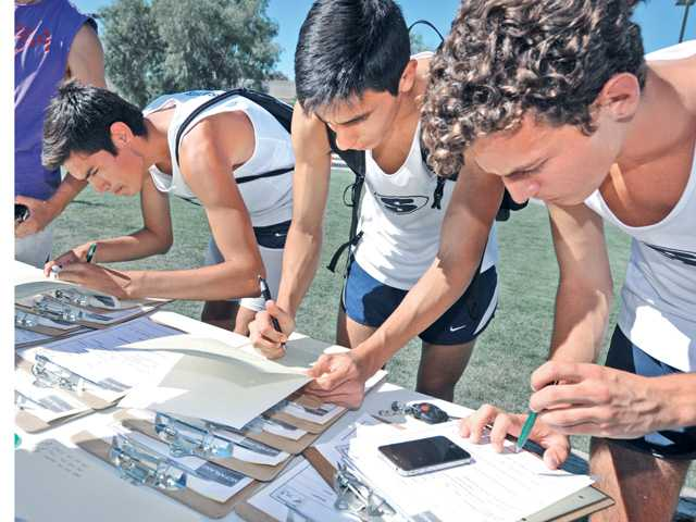 "Saugus High School graduates, from left, Pablo Velero, Rodrigo Ornelus and Anthony Janaslani sign up for tryouts for cross country runners in the Disney film ""McFarland."" Signal photo by Dan Watson"