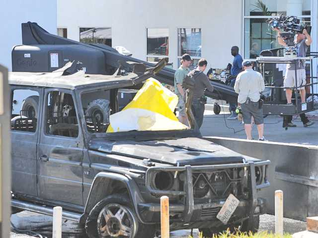A camera crew works around the burned out hulk of a vehicle during movie filming at 24030 Creekside Road in Valencia on Thursday.