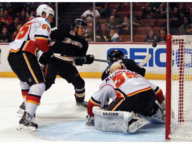 Anaheim Ducks right wing Emerson Etem, second from left, attempts to hit the puckin the goal as the Calgary Flames defend on Wednesday in Anaheim.