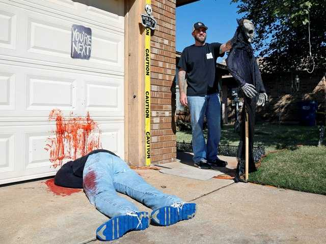Johnnie Mullins poses with his controversial Halloween display featuring a headless, bloodied dummy dressed in his work clothes at his home.