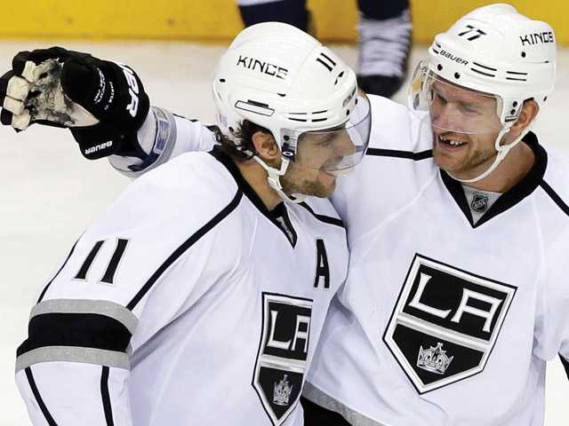 Los Angeles Kings center Anze Kopitar (11), of Slovenia, celebrates with Jeff Carter (77) after scoring against the Nashville Predators during the shootout in an NHL hockey game Thursday, Oct. 17, 2013, in Nashville, Tenn. The Kings won 2-1.