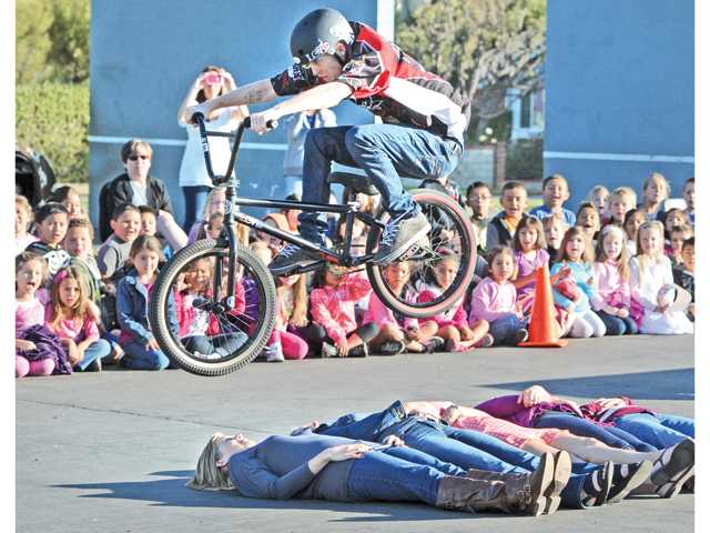 Dozens of students look on as Andrew Johnson of BMX Pros jumps his bike over five teachers lying on the playground at Valencia Valley Elementary School on Friday. Two professonal BMX riders spoke about maintaining a healthful, drug-free lifestyle during the National Red Ribbon Campaign kickoff event. Signal photo by Dan Watson