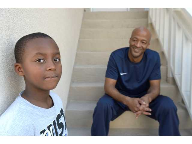 John Cotton Sr., right, sits with his son, John Cotton, Jr., in their Cypress, Calif. home on Thursday, Oct. 17, 2013.