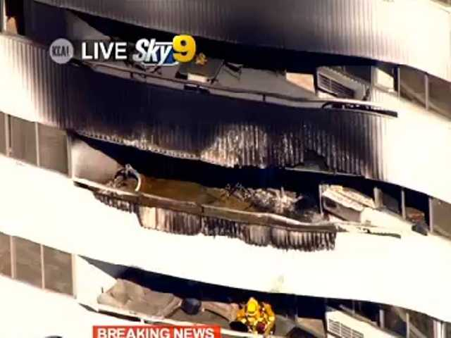 "A video image by KCAL-TV shows a fire-damaged high rise apartment building in L.A. Friday. Three people were taken to the hospital and ""a handful"" of others were treated."