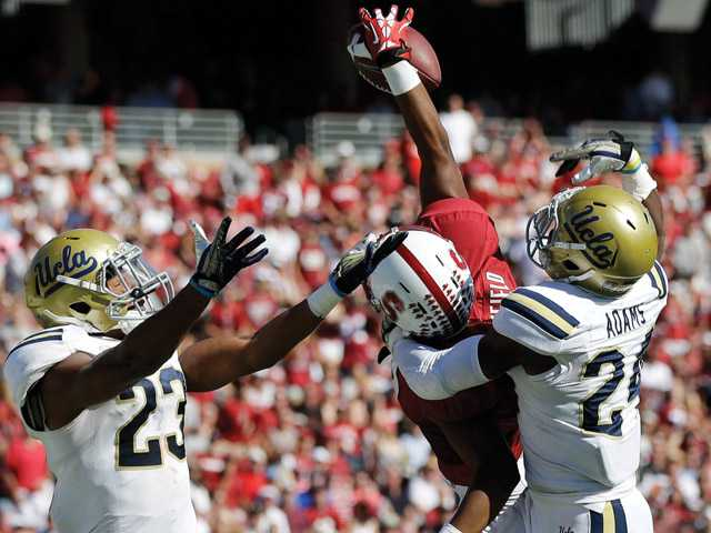 Stanford wide receiver Kodi Whitfield, center makes a one-handed touchdown catch next to UCLA cornerback Ishmael Adams, right, and cornerback Anthony Jefferson during the second half of an NCAA college football game on Saturday, Oct. 19, 2013, in Stanford, Calif. Stanford won 24-10.