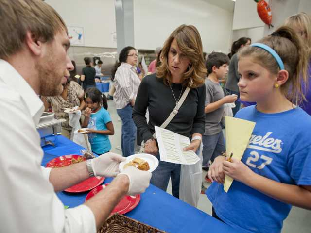 A representative from Buena Vista Food Products offers Lisa Ziegler and her daughter Julia samples at the Santa Clarita Valley School Food Services Agency vendor show. Photo by Charlie Kaijo.
