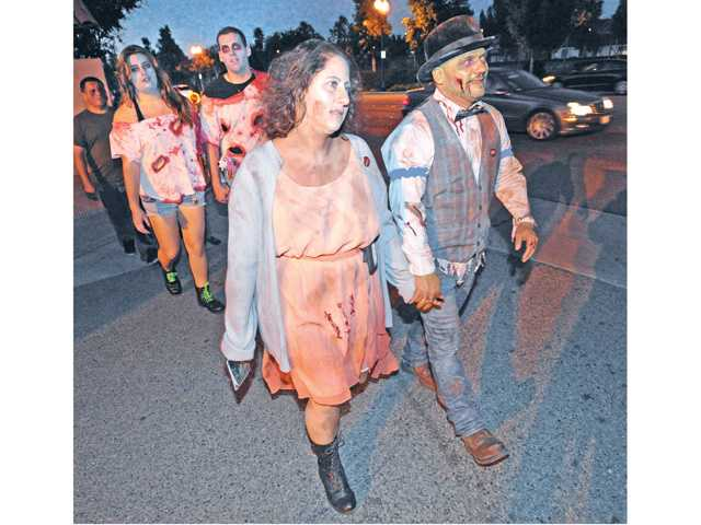 Jennifer Solotkin, left, and Mathew Moore walk as a dead couple during the Zombie Walk which culminated at Heritage Haunt held at Heritage Junction at William S. Hart Park in Newhall on Saturday.
