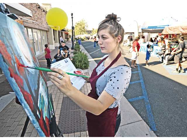 Artist and art instructor Jillian Luz creates a sample painting at the Pinot's Palette booth during the SCV Chamber Home and Business Expo on Main Street in Newhall on Saturday.