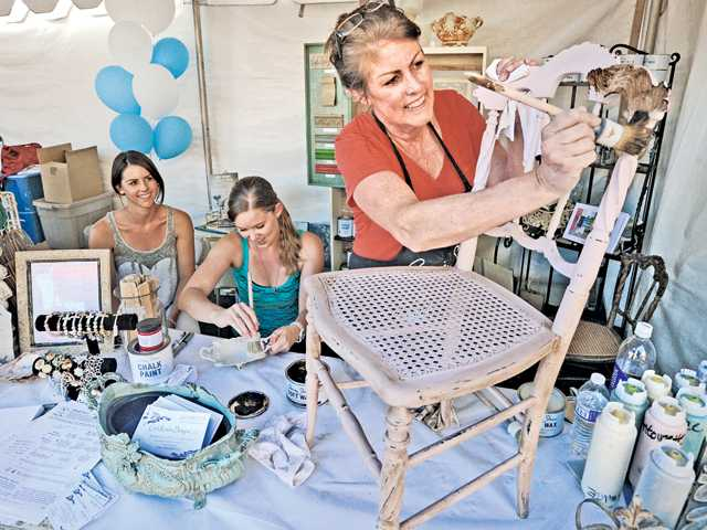 Cindy Rowley, right, demonstrates her chalk paint on an antique chair as Casey Rowley, left, and Kayleen Murphy apply the paint on antique silver ware at the Cindy Rowley Designs booth during the SCV Chamber Home and Business Expo held on Main Street in Newhall on Saturday.