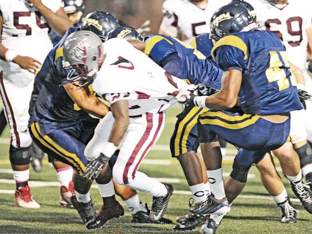 College of the Canyons' Wes Johnson (47), right, and his teammates bring down Antelope Valley College running back Ron Howard (22) for a loss in the third quarter at COC on Saturday, Oct. 12.