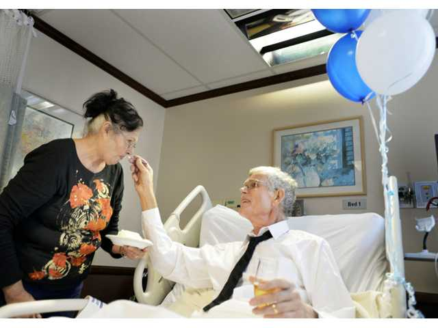 Dennis Lyman, right, feeds wedding cake to his new bride Barbara Lyman, right, shortly after their wedding ceremony Friday in the chapel of St. Joseph hospital in Orange.