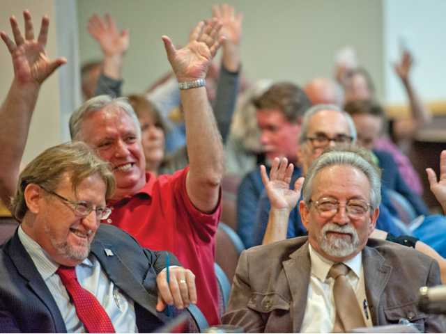 Audience members, including City Councilman TimBen Boydston (front left), raise their hands in silent applause for a point made during a Board of Directors meeting addressing chloride level compliance at City Hall on Tuesday. Photo by Charlie Kaijo.