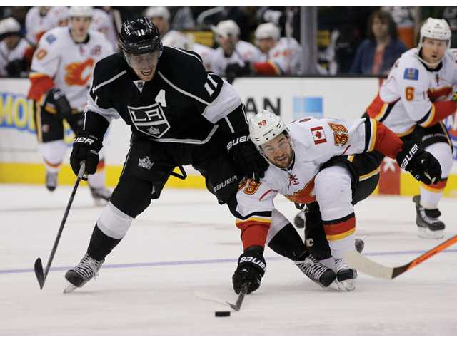 Los Angeles Kings center Anze Kopitar, left, battles Calgary Flames left wing T.J. Galiardi on Monday in Los Angeles.