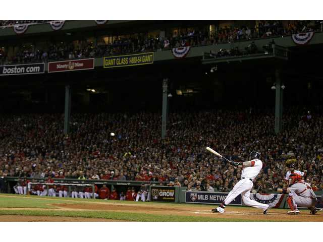 Boston Red Sox's Mike Napoli hits a three-run double during the first inning of Game 1 of baseball's World Series against the St. Louis Cardinals Wednesday.