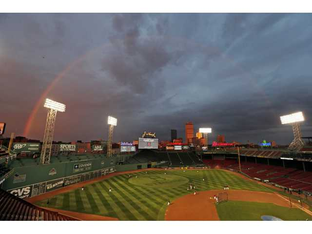 Boston Red Sox players take batting practice as a rainbow appears in the sky above Fenway Park on Tuesday in Boston.