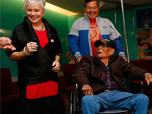Michael Coon, top, smiles as his father Phillip Coon, in wheelchair, receives military honors from Rita Aragon, secretary of Military and Veterans Affairs for the State of Oklahoma, after Phillip's return from Japan, where he was a POW, at the Tulsa International Airport, on Monday.
