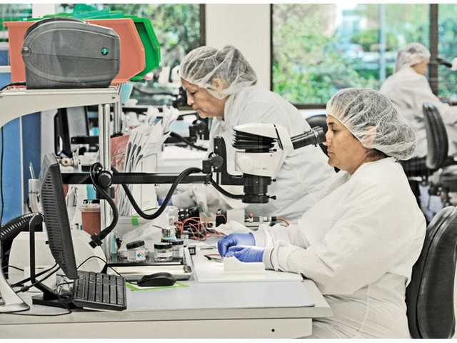 Workers assemble pieces of the cochlear implant in the Advanced Bionics Electrode Assembly Clean Room at headquarters in Valencia.