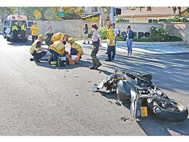 Los Angeles County Fire paramedics tend to an injured female motorcyclist after she collided with another vehicle at Via Princessa and Via Pacifica on Wednesday. The woman was taken to Henry Mayo Newhall Memorial Hospital. Photo by Rick McClure for The Signal.