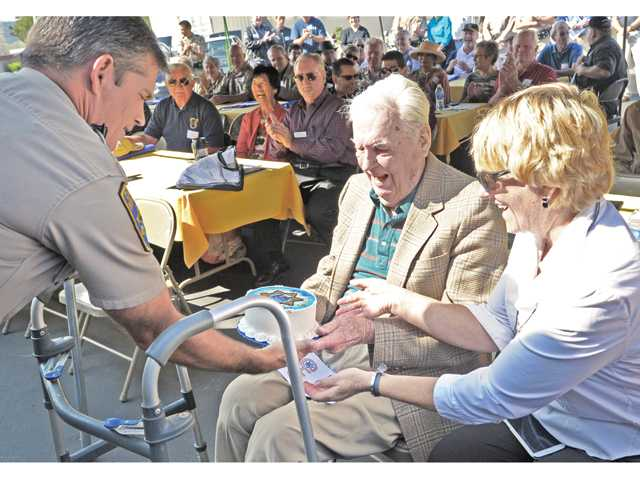Dozens of attendees look on as California Highway Patrol Officer John Lutz, left, presents a birthday cake to retired CHP Commissioner Harold Sullivan, center, in celebration of his 101st birthday at the CHP Southern Division Retiree Day held at the CHP Newhall Station on Thursday. Daughter-in-law Stevi Sullivan looks on.