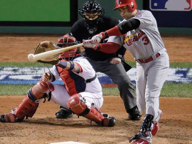 St. Louis Cardinals' Carlos Beltran hits an RBI single in front of Boston Red Sox catcher Jarrod Saltalamacchia during the seventh inning in Game 2 of baseball's World Series Thursday, Oct. 24, 2013, in Boston.