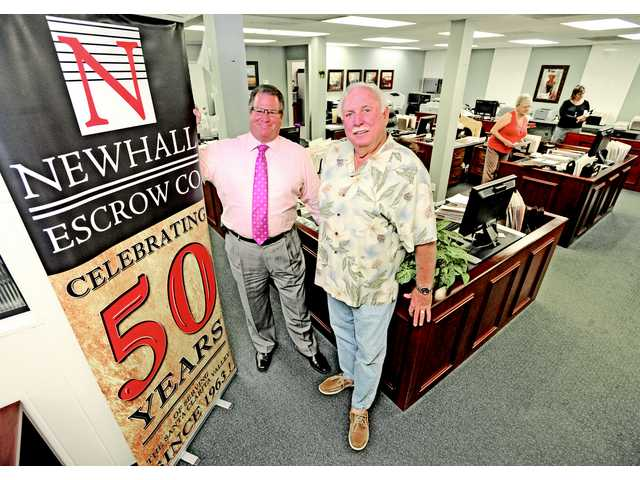 Steve Corn and father Ron stand alongside in escrow office in Newhall. Newhall Escrow is the oldest escrow company operating in Santa Clarita. The company will celebrate its 50th anniversary on December 19, 2013.