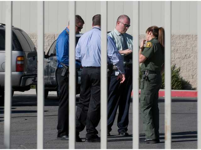 San Bernardino County Sheriff's Homicide Division detectives and scientific investigations workers meet at the Materials Recycling Facility in Victorville, Calif., on Thursday, Oct. 24.