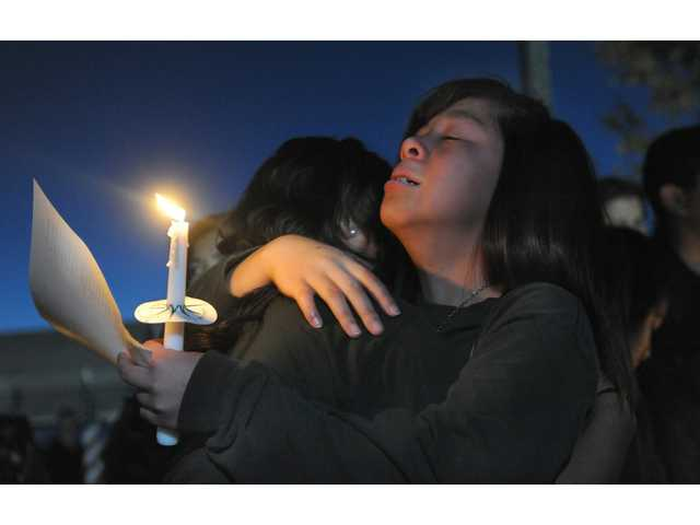 Jannelle Tan grieves for her teacher Michael Landsberry during a vigil held at Sparks Middle School on Wednesday, Oct. 23, 2013 in Sparks, Nev.