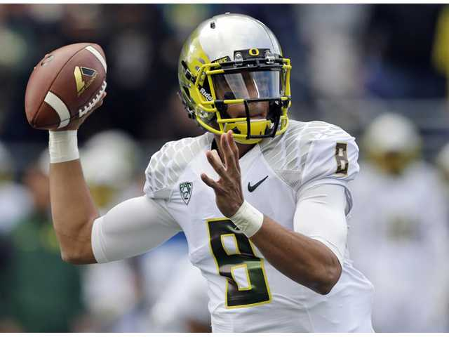 Oregon quarterback Marcus Mariota throws a pass against Washington in the first half of an NCAA college football game in Seattle.
