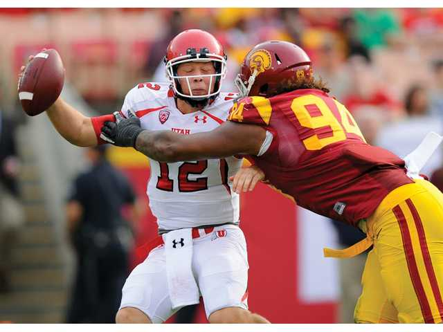 Utah quarterback Adam Schulz (12) is sacked by USC defensive end Leonard Williams (94) on Saturday in Los Angeles.