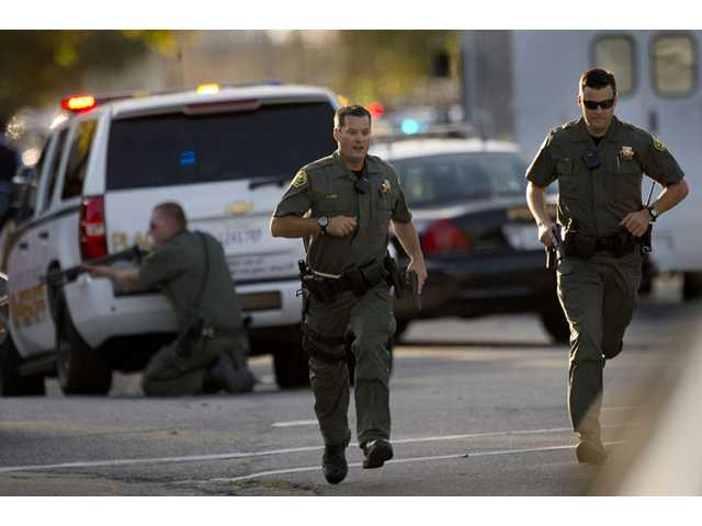 Police converge on a house where Sammy Duran is suspected to be residing on Friday, Oct. 25, 2013, in Roseville, Calif.