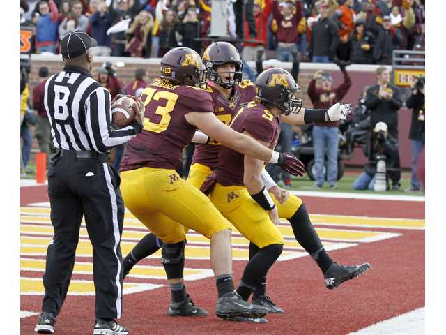 Minnesota tight end Drew Goodger (83) and wide receiver Drew Wolitarsky (82), a Canyon High graduate, congratulate quarterback Philip Nelson (9) after his touchdown in the fourth quarter against Nebraska in Minneapolis on Saturday.