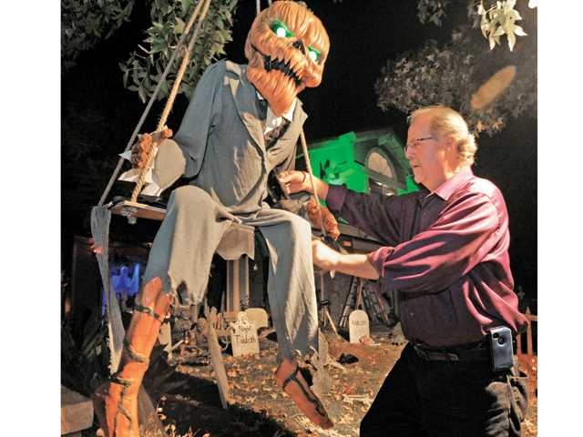 Rob Tezai puts final touches on a talking pumpkin-head man that sits on a swing in his front yard on Rodeffer Place near Copper Hill in Saugus, as he prepares his Halloween display.