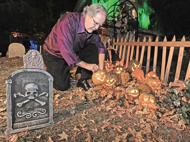 "Rob Tezai hooks up pumpkins on his front lawn on Rodeffer Place near Copper Hill in Saugus as he prepares his decorations for Halloween. The front yard's creepy Halloween-themed decor derives from a variation of the quote from Edger Allan Poe's ""The Raven"": ""Never gore."" It's recommended for all ages."