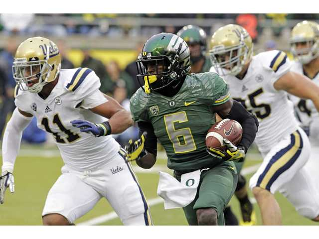 Oregon running back DeAnthony Thomas, middle, turns the corner against UCLA defenders Anthony Barr, left, and Jordan Zumwalt on Saturday in Eugene, Ore.