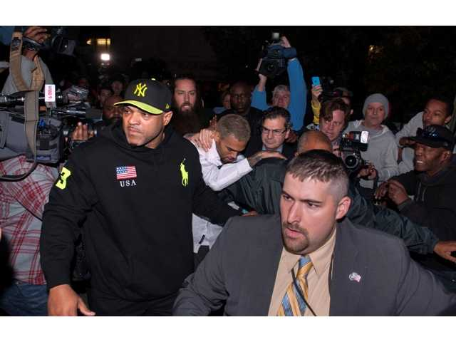 Singer Chris Brown is surrounded by bodyguards as he departs the H. Carl Moultriel courthouse Monday, Oct. 28, 2013, in Washington.