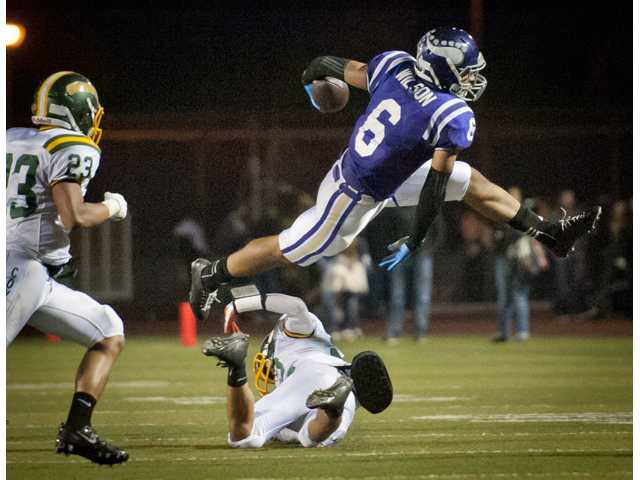 Valencia wide receiver Jay Jay Wilson leaps over a Canyon defender during Friday's game at Valencia High School.