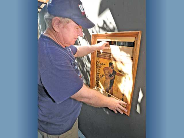 Cal Liedtke tests one of the sliding picture frames that will reveal a live ghoul on Halloween night at his haunted house. Photo by Dan Watson.