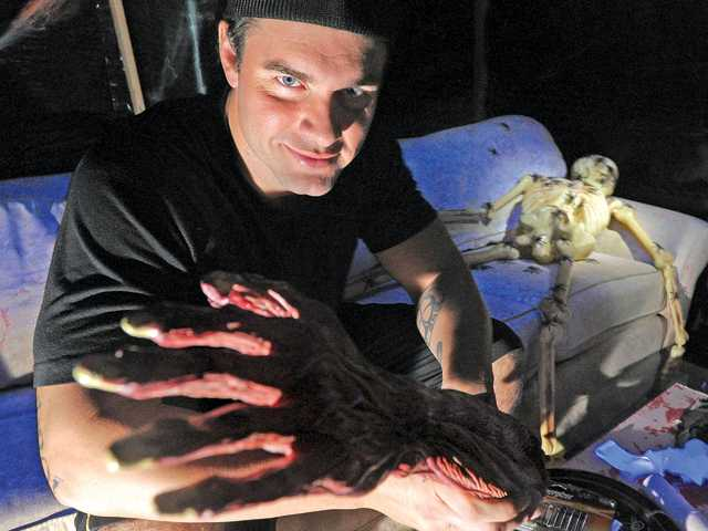 "Adam Hatley rearranges body parts in the spider room of his haunted house in Newhall. Hatley has constructed the display— dubbed ""Just Scream"" this year — for the past three Halloweens. Photo by Dan Watson."