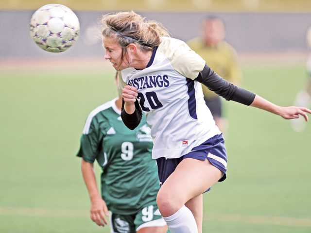 The Master's College's Gabrielle Arnone (20) heads a shot on goal against Concordia at TMC on Tuesday.