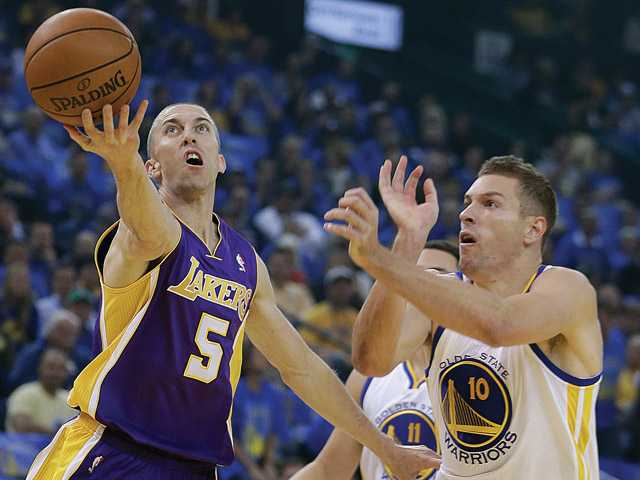 Los Angeles Laker Steve Blake (5) lays up a shot against Golden State Warriors' David Lee, right, during the first half on Wednesday in Oakland.